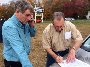 Glastonbury businessman Bruce Bemer (left) fills out paperwork with attorney Garon Camassar after Bemer was the high bidder in a foreclosure auction Saturday of the Waterford Speedbowl